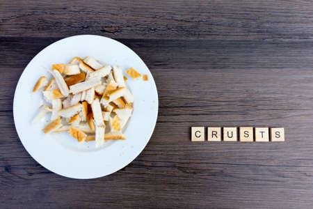 Plate of white bread crusts with the word crusts - copy space provided