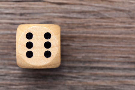 Wooden dice with number 6, pictured against a wooden background