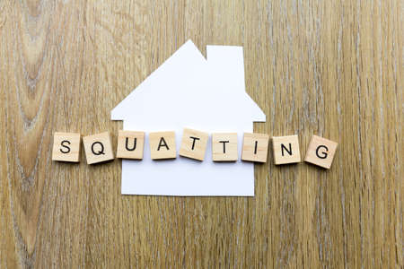 Squatting concept - paper house with the word 'squatting'' 版權商用圖片