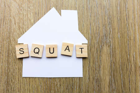 Squatting concept - paper house with the word squat Фото со стока