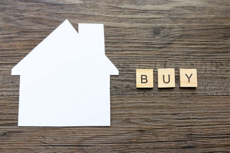 House Buying Concept - Paper house with the word Buy Фото со стока