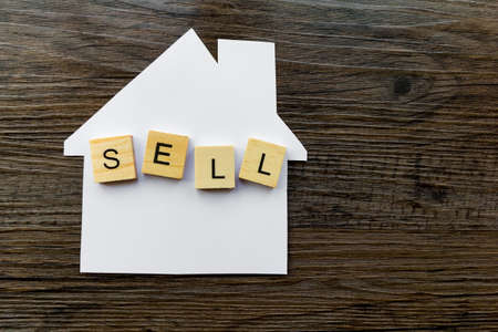 House Selling Concept - Paper house with the word Sell Фото со стока