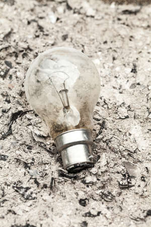 Old fashioned filament lightbulb on a pile of ashes Stock Photo