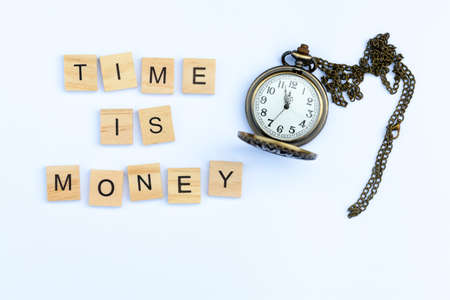 The words time is money on a white background with an old fashioned pocket watch Фото со стока