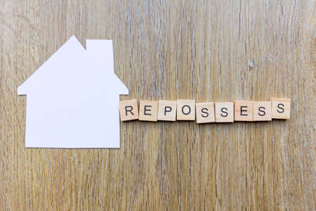 House repossession concept - paper house with the word repossess Фото со стока