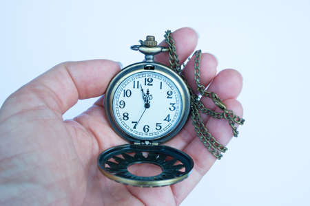Holding a vintage pocket watch showing the time close to 12 oclock Фото со стока