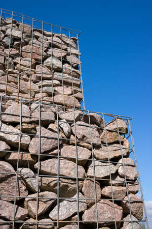 Gabion wall or tower against a blue sky background