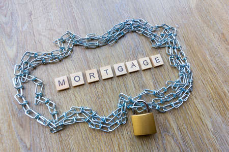 Mortgage debt concept - chain surrounding a house with the word mortgage