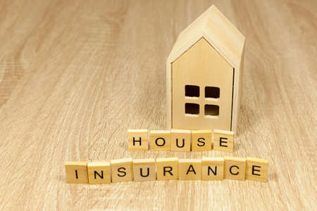 The words house insurance in front of a small wooden house - copy space provided