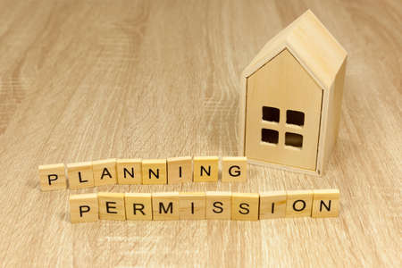 The words 'planning permission' in front of a small wooden house - copy space provided Imagens