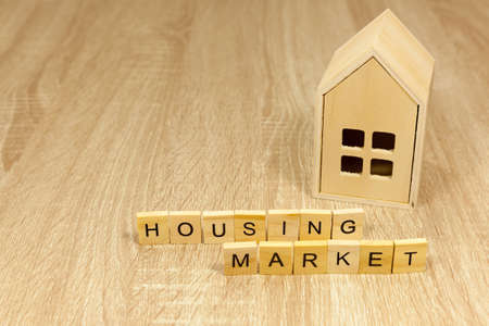 The words housing market in front of a small wooden house - copy space provided