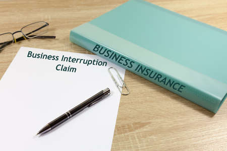 Business Interruption Claim Concept - with folder that reads 'Business Insurance'