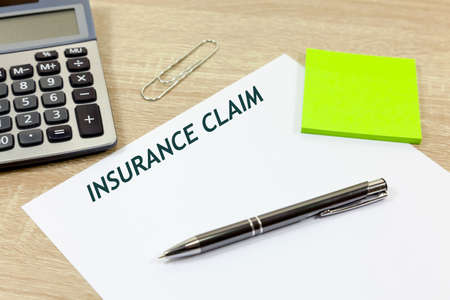 Paper with the title 'Insurance Claim' with pen and calculator