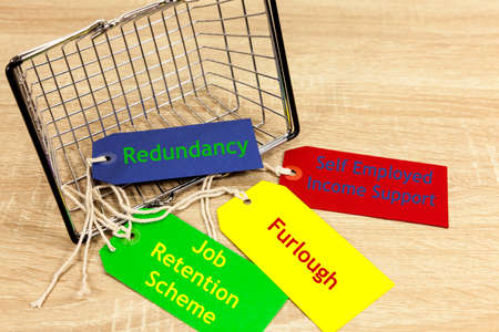 Concept of work issues relating to the coronavirus pandemic - shopping basket and labels with work related phrases