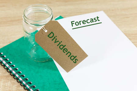 Empty jar with label that reads 'Dividends' alongside paper document with the word 'Forecast'