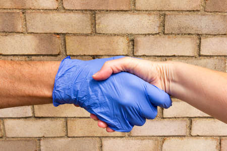 Hand Protection and Disease Spreading Concept - one person wearing protective gloves and other person with no gloves Archivio Fotografico