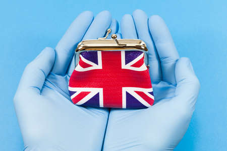 UK Hospital Funding Concept - Union jack purse held in hands wearing hospital gloves Archivio Fotografico