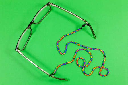 A pair of glasses with multi-coloured beaded neck cord attached Archivio Fotografico