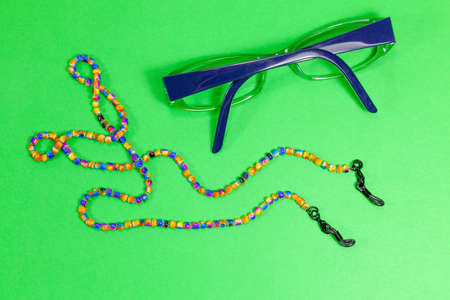 A pair of glasses with multi-coloured beaded neck chain Archivio Fotografico