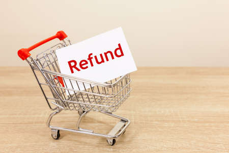 Shopping trolley carrying the word refund - copy space provided Archivio Fotografico