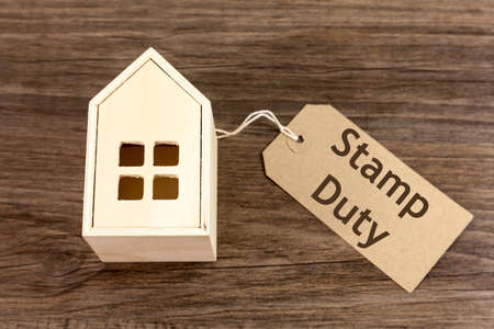 Wooden house with label attached which reads 'Stamp Duty' Archivio Fotografico