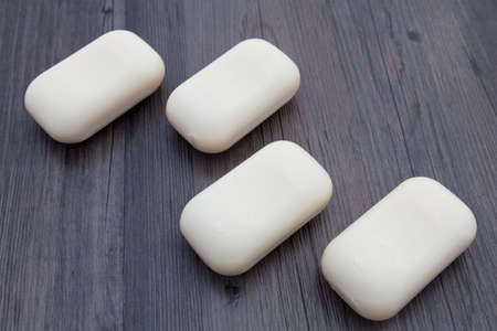 Bars of plain soap on a dark wood background
