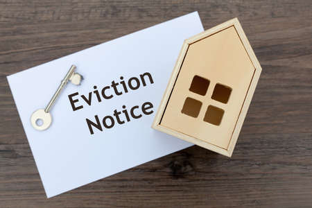 Eviction Notice written on an envelope alongside a key and wooden toy house