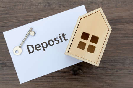 Envelope with the word 'deposit' along with a house key and toy wooden house