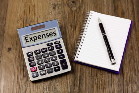 Expenses concept - the word 'expenses' written on calculator, alongside note pad and pen Archivio Fotografico