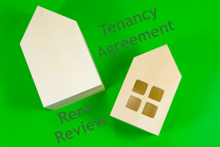 The words 'Tenancy Agreement' and 'Rent Review' written alongside model wooden houses