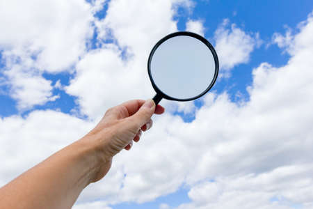Person holding a magnifying glass to the sky,