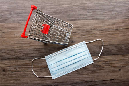 Conceptual for face mask and shopping - Miniature shopping trolley and a face mask together on a dark wood background