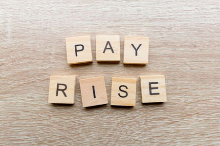 The words 'Pay Rise' on a wooden background