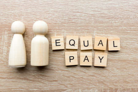 Male and female wooden figures and the message 'equal pay'