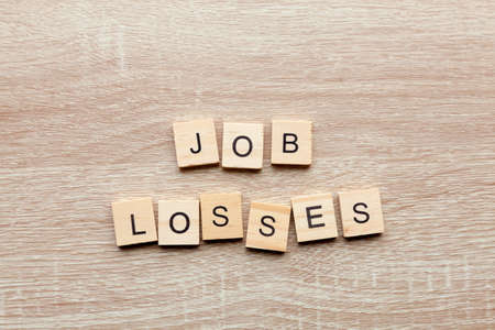 The phrase 'job losses' on a light wood background
