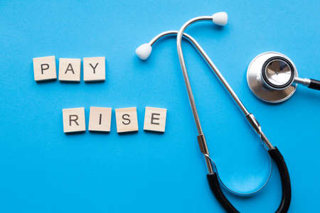 Wages concept for medical staff - The words 'Pay Rise' alongside a stethoscope Archivio Fotografico