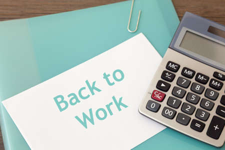 Folder with calculator and document which reads 'back to work'