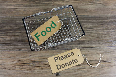 Food Poverty Concept - Shopping basket with message 'please donate' 스톡 콘텐츠