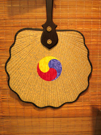 a traditional korean fan hanging on a wall