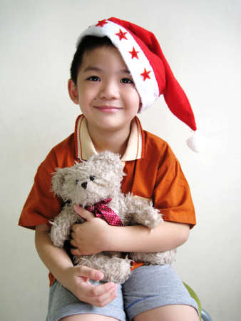 cuteness: a asian boy wearing santa hat and holding a bear
