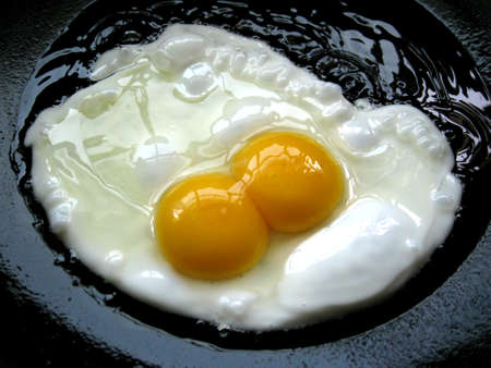 Fried egg with two egg yolk on the black background Stock Photo