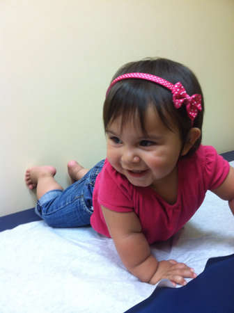 10 months old happy at the doctors offices waiting for her shots  Banco de Imagens