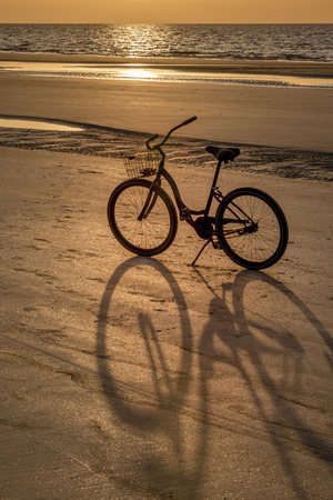 One, purple beach cruiser bicycle casts a shadow on the glittery sand during a peaceful, ocean sunrise or golden sunset during spring break or summer vacation. Recreation concept.
