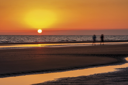 Sunrise with vibrant yellow, orange and pink colors on an ocean beach as two blurred joggers get their morning exercise at low tide. Stock Photo
