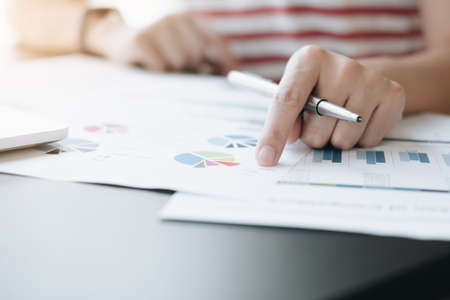 Close up of Business woman investment consultant analysis company annual financial report balance sheet statement working with documents graphs. Concept picture of economy, marketing