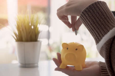 A woman putting coin in yellow piggy bank while using laptop for calculator money saving - Financial Saving Concept Stock fotó - 133414815