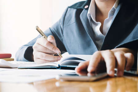 Businesswoman working on smartphone and writing down notes on notebook. Business planning and organization, paperwork concept