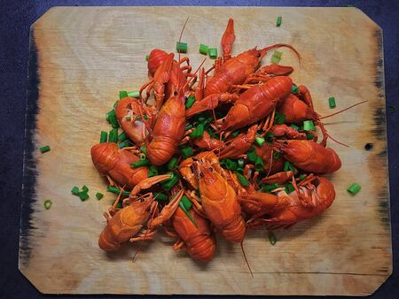 photo cooked red boiled crayfish with sliced green onions on a wooden Board. Arthropods are animals. Shiny carapaces. Large claws. Long mustache. Beer snack