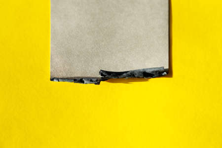 craft page with burned edge on yellow background. 版權商用圖片
