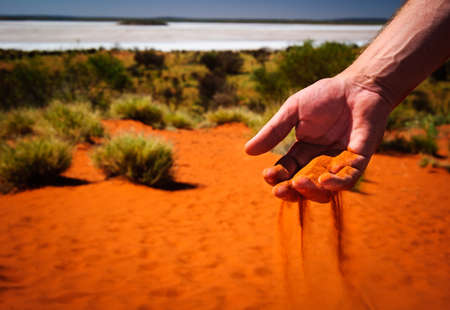australia outback red sand through hand photo